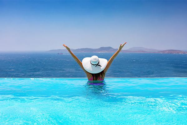 Mujer contemplando el Mediterráneo desde la piscina infinity