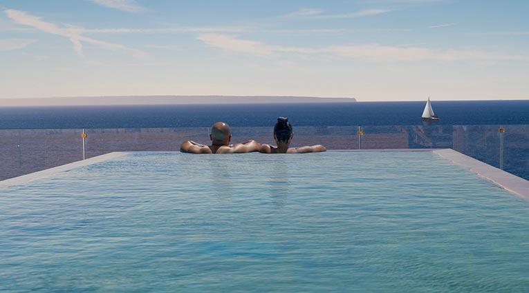 Pareja de huéspedes disfrutando de las vistas al mar mediterráneo en la skypool