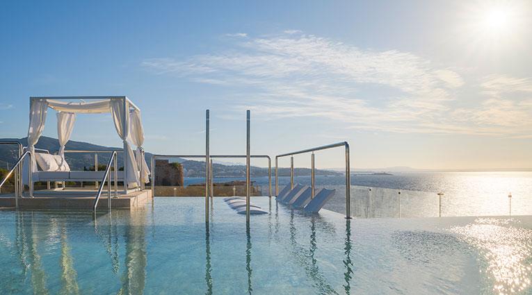 Vista de la piscina infinity con cama balinesa y cielo de fondo