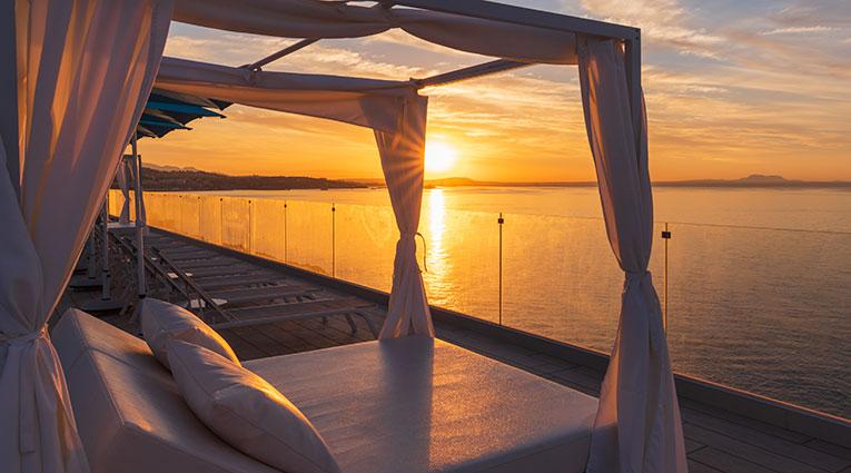 Amanecer desde cama balinesa en la terraza de la piscina infinity