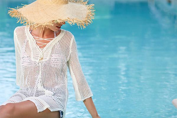 Mujer con pamela sentada en la piscina skypool