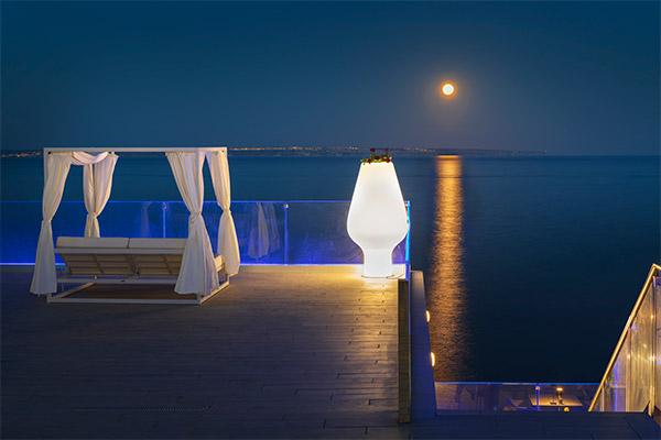 Cama balinesa con luna de fondo y reflejo en el agua