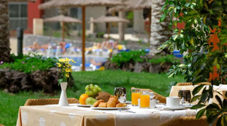 Desayuno con vista del jardín y la piscina