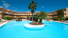 Vista de la piscina del hotel con el edificio principal de fondo