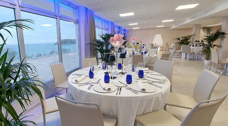 Vista de salón con mesas montadas para banquetes