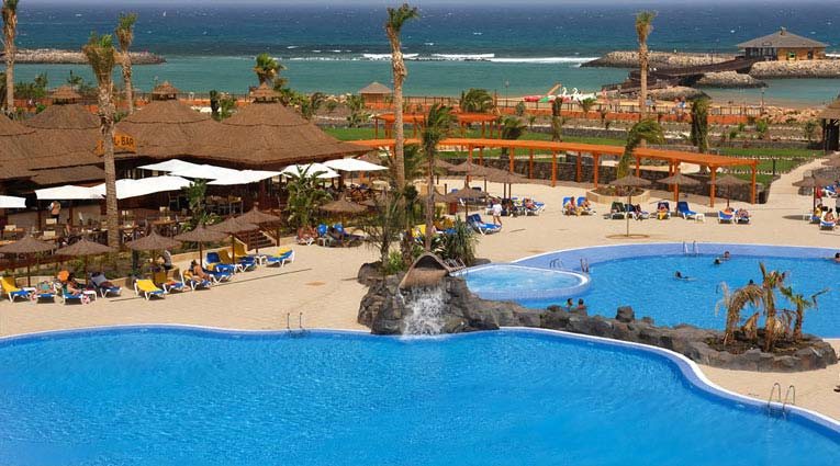 vista general de la piscina del hotel con el mar de fondo