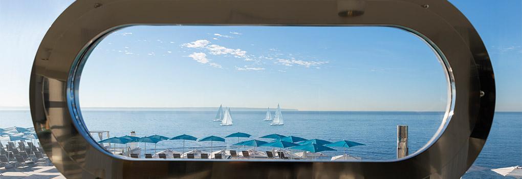 Vista del mediterráneo desde ventana tipo escotilla en la recepción del hotel