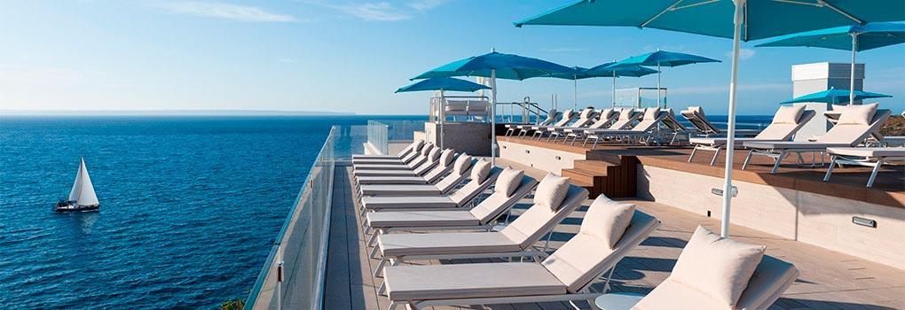 Vista de tumbonas en la terraza de la piscina infinity con vistas al mediterráneo y barco de fondo