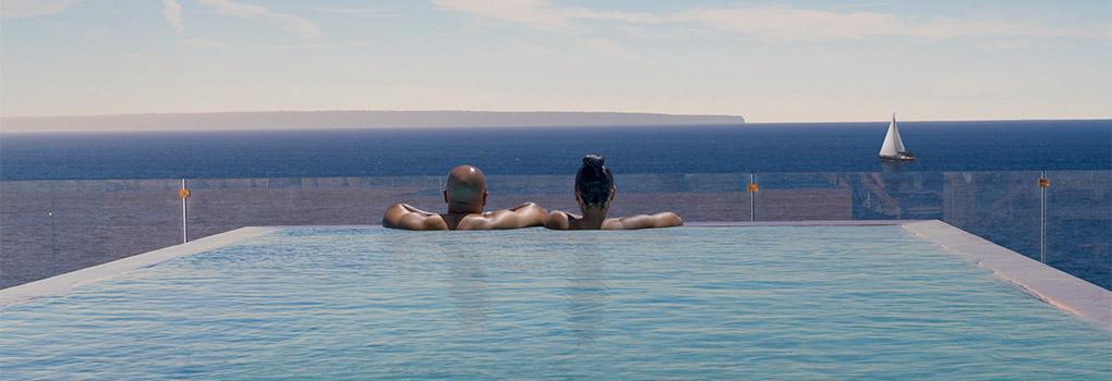Pareja de huéspedes disfrutando de las vistas en la piscina infinity