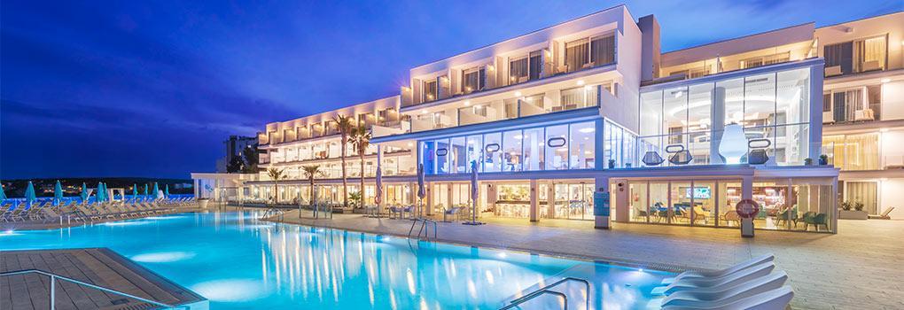 Vista atardecer de la fachada del hotel frente piscina principal