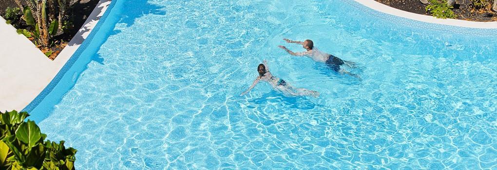 Vista aérea de pareja nadando en la piscina