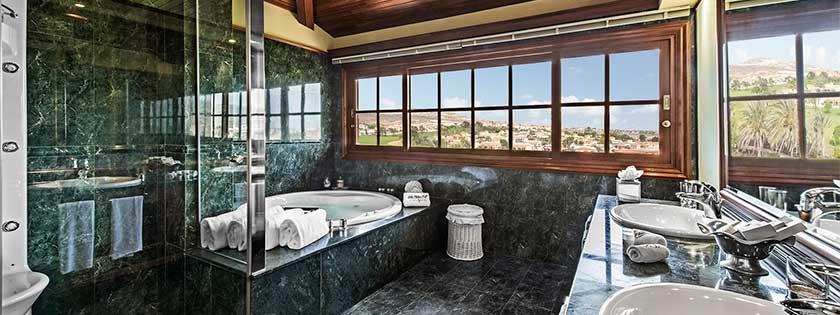 Baño con ducha hidromasaje y bañera en la Suite del Elba Palace